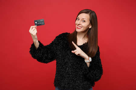 Attractive young woman in black fur sweater pointing index finger on credit bank card isolated on bright red wall background in studio. People sincere emotions, lifestyle concept. Mock up copy space Stockfoto
