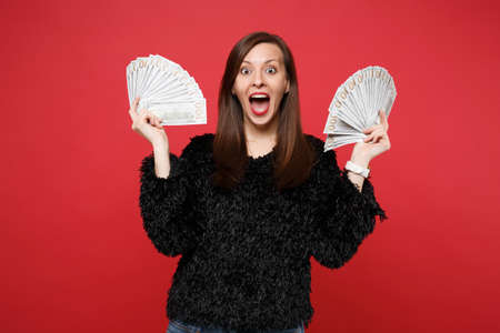 Surprised young woman in fur sweater with opened mouth holding fan of money in dollar banknotes, cash money isolated on red background. People sincere emotions, lifestyle concept. Mock up copy space