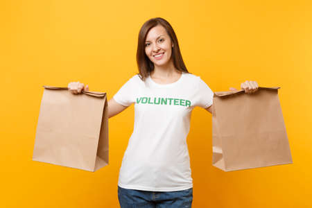 Portrait of woman in white t-shirt written inscription green title volunteer hold blank craft paper bag for takeaway isolated on yellow background. Voluntary free assistance charity grace concept Imagens