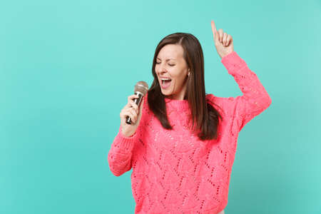 Pretty young woman in knitted pink sweater dancing, pointing index finger up, sing song in microphone isolated on blue wall background, studio portrait. People lifestyle concept. Mock up copy space Stockfoto