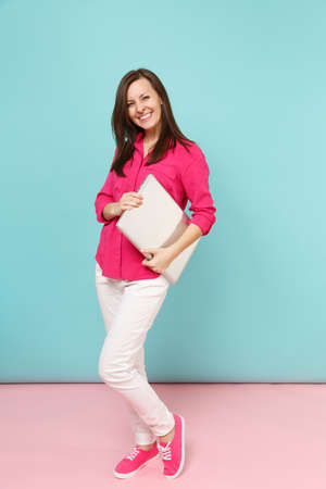 Full length portrait young woman in rose shirt blouse, white pants holding laptop pc computer isolated on bright pink blue pastel wall background studio. Fashion lifestyle concept. Mock up copy space Stock fotó