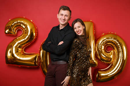 Couple guy girl in shiny glitter dress, black shirt celebrating holiday party isolated on bright red wall background golden numbers air balloons studio portrait. Happy New Year 2019 Christmas concept