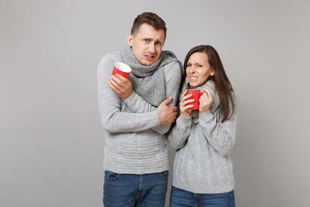 Couple girl guy in gray sweaters, scarves hold cups with tea isolated on grey wall background, studio portrait. Healthy lifestyle, ill sick disease treatment, cold season concept. Mock up copy space Stockfoto