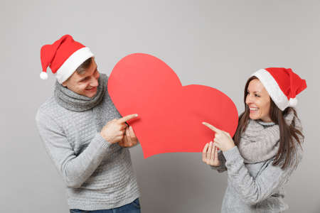 Merry fun couple girl guy in red Santa Christmas hat gray sweaters scarves isolated on grey wall background, studio portrait. Happy New Year 2019 celebration holiday party concept. Mock up copy space