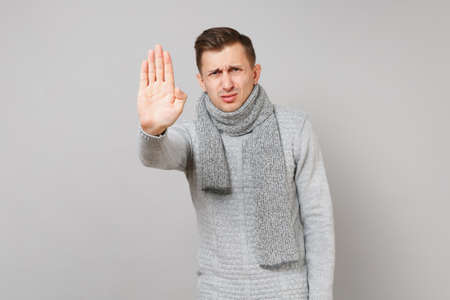 Dissatisfied young man in gray sweater, scarf showing stop gesture with palm isolated on grey background. Healthy fashion lifestyle, people sincere emotions, cold season concept. Mock up copy space
