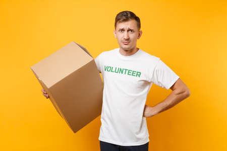 Portrait of confused man in white t-shirt with written inscription green title volunteer with big cardboard box isolated on yellow background. Voluntary free assistance help, charity grace concept
