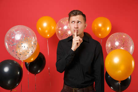 Bewildered young man in black classic shirt saying hush be quiet with finger on lips, shhh gesture on red background air balloons. Valentine's Day Happy New Year birthday mockup holiday party concept