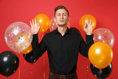 Calmed young man in black classic shirt meditate spreading hands on bright red background air balloons. St. Valentine's International Women's Day, Happy New Year birthday mockup holiday party concept
