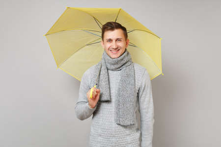 Smiling young man in gray sweater, scarf holding yellow umbrella isolated on grey background studio portrait. Healthy fashion lifestyle people sincere emotions cold season concept. Mock up copy space