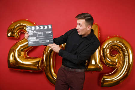 Man in black shirt celebrating holiday party, hold film making clapperboard isolated on bright red wall background, golden numbers air balloons studio portrait. Happy New Year 2019 Christmas concept Stock Photo