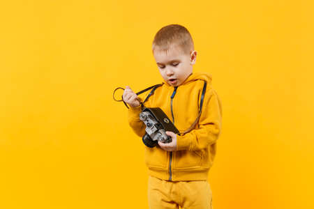 Little kid boy 3-4 years old wearing yellow clothes hold camera isolated on orange wall background, children studio portrait. People sincere emotions, childhood lifestyle concept. Mock up copy space