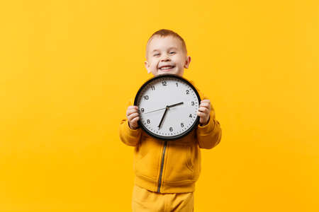 Little kid boy 3-4 years old wearing yellow clothes hold clock isolated on orange wall background, children studio portrait. People sincere emotions, childhood lifestyle concept. Mock up copy space Banque d'images - 115234845