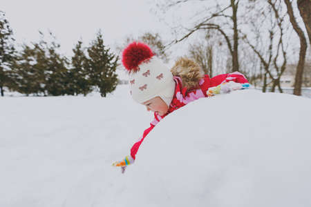 Smiling little girl in winter warm clothes and hat playing and making snowball in snowy park or forest outdoors. Winter fun, leisure on holidays. Love relationship family childhood lifestyle concept