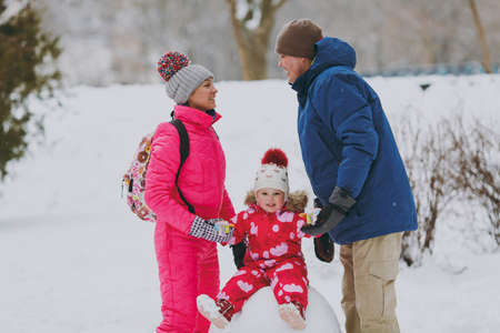 Happy family woman, man in winter warm clothes and little girl sitting on snowball in snowy park or forest outdoors. Winter fun, leisure on holidays. Love relationship family people lifestyle concept
