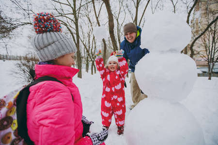 Happy family man, woman little girl in warm clothes throwing snowball, making snowman in park or forest outdoors. Winter fun, leisure on holidays. Love relationship family people lifestyle concept