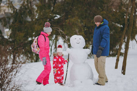 Happy young family man, woman little girl in warm clothes standing near snowman in snowy park or forest outdoors. Winter fun, leisure on holidays. Love relationship family people lifestyle concept Stock Photo