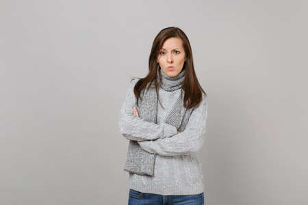 Perplexed concerned young woman in gray sweater, scarf hold hands folded isolated on grey wall background. Healthy fashion lifestyle, people sincere emotions, cold season concept. Mock up copy space