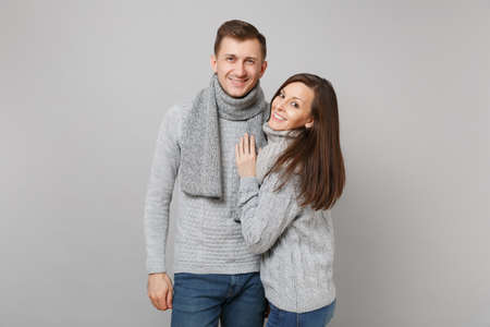 Young cute couple girl guy in gray sweaters, scarves together isolated on grey wall background, studio portrait. Healthy lifestyle, ill sick disease treatment, cold season concept. Mock up copy space