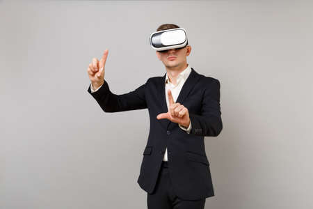 Young business man in suit looking in headset touch something like push click on button and pointing at floating virtual screen isolated on grey background. Achievement career wealth business concept 版權商用圖片