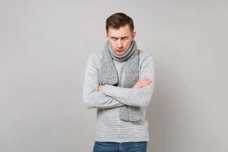 Strict young man in gray sweater, scarf holding hands crossed isolated on grey wall background in studio. Healthy fashion lifestyle, people sincere emotions, cold season concept. Mock up copy space 스톡 콘텐츠
