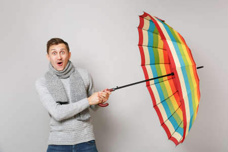 Surprised young man in gray sweater, scarf keeping mouth wide open, holding colorful umbrella isolated on grey wall background. Healthy fashion lifestyle, people sincere emotions, cold season concept 免版税图像