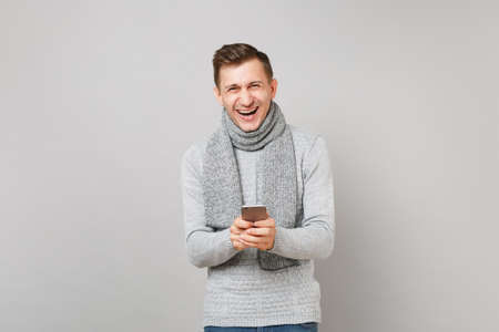 Laughing young man in gray sweater, scarf using mobile phone, typing sms message isolated on grey background. Healthy fashion lifestyle people sincere emotions cold season concept. Mock up copy space