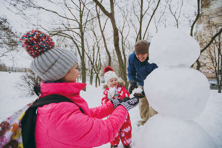Happy family man, woman little girl in warm clothes play making snowballs, snowman in snowy park or forest outdoors. Winter fun, leisure on holidays. Love relationship family people lifestyle concept Stock Photo
