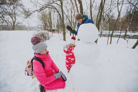 Cheerful family man woman, little girl in winter warm clothes play, making snowman in snowy park or forest outdoors. Winter fun, leisure on holidays. Love relationship family people lifestyle concept