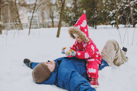 Happy family lying man, little girl in colorful warm clothes sitting playing, making snowball in snowy park or forest outdoors. Winter fun, leisure on holidays. Love relationship lifestyle concept