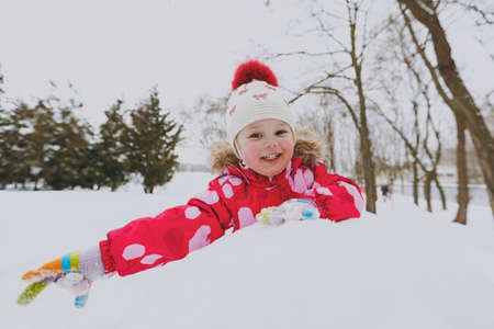 Happy little girl in winter warm clothes and hat playing and making snowball in snowy park or forest outdoors. Winter fun, leisure on holidays. Love relationship family childhood lifestyle concept