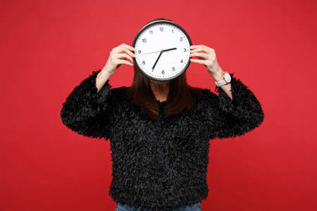Portrait of young woman in black fur sweater hiding, covering face with round clock isolated on bright red wall background in studio. Time is running out. People lifestyle concept. Mock up copy space