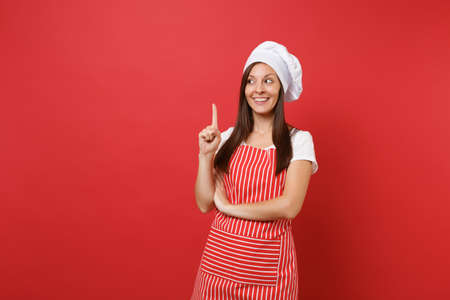 Housewife female chef cook or baker in striped apron, white t-shirt, toque chefs hat isolated on red wall background. Beautiful housekeeper woman pointing index finger up. Mock up copy space concept