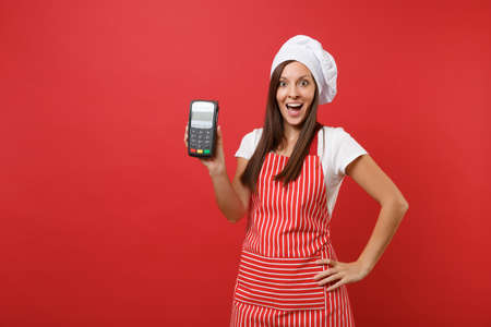 Housewife female chef cook or baker in striped apron t-shirt toque chefs hat isolated on red wall background. Woman hold in hand wireless bank payment terminal nfc device. Mock up copy space concept