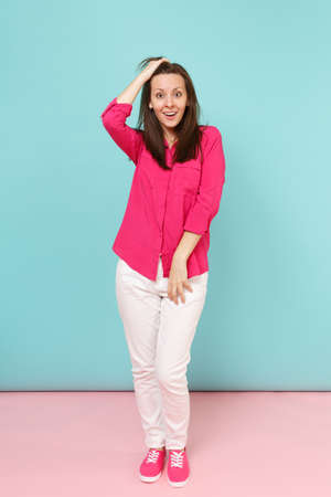Full length portrait of smiling young pretty woman in rose shirt blouse, white pants posing isolated on bright pink blue pastel wall background studio. Fashion lifestyle concept. Mock up copy space Stock Photo