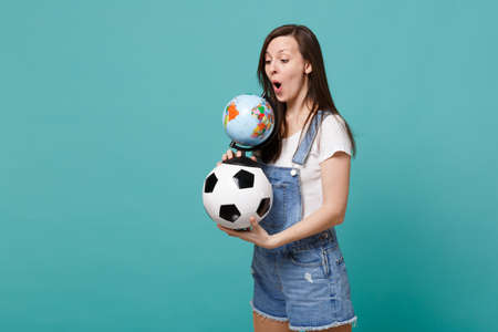 Shocked young woman football fan holding soccer ball, looking on Earth world globe isolated on blue turquoise background. People emotions, sport family leisure lifestyle concept. Mock up copy space