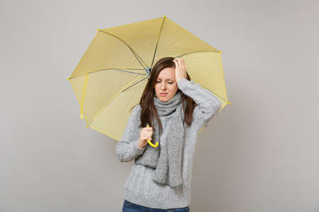 Upset tired young woman in gray sweater, scarf putting hand on head, holding yellow umbrella isolated on grey background in studio. Healthy lifestyle, ill sick disease treatment, cold season concept