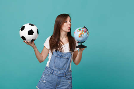 Curious young girl football fan support favorite team with soccer ball, Earth world globe isolated on blue turquoise wall background. People emotions, sport family leisure concept. Mock up copy space