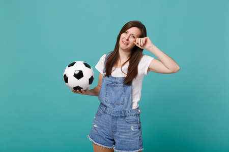 Crying distempered young woman football fan support favorite team with soccer ball wiping tears isolated on blue turquoise wall background. People emotions, sport family leisure lifestyle concept