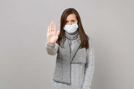 Young woman in sweater, scarf with sterile face mask showing stop gesture with palm isolated on grey background. Healthy lifestyle, ill sick disease treatment, cold season concept. Mock up copy space Foto de archivo
