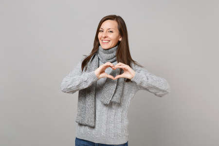 Smiling young woman in gray sweater, scarf showing shape heart with hands isolated on grey wall background. Healthy fashion lifestyle, people sincere emotions, cold season concept. Mock up copy space