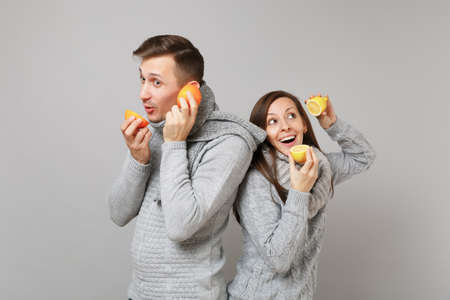 Fun couple girl guy in gray sweaters, scarves together hold orange lemon isolated on grey wall background studio portrait. Healthy lifestyle ill sick treatment cold season concept. Mock up copy space
