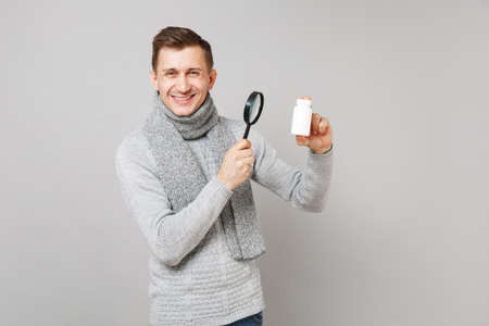 Smiling young man in gray sweater, scarf holding medication tablets, aspirin pills in bottle and magnifying glass isolated on grey background. Health, ill sick disease treatment cold season concept