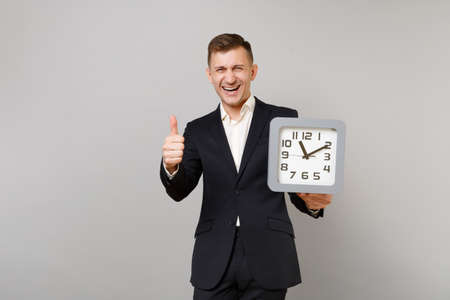 Laughing young business man in classic black suit, white shirt holding square clock, showing thumb up isolated on grey wall background. Achievement career wealth business concept. Mock up copy space