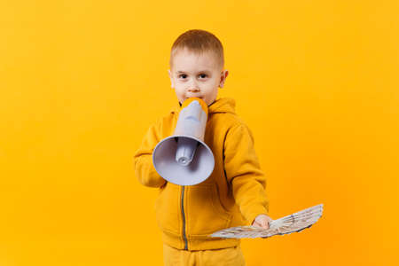 Little happy kid boy in yellow clothes hold fan of money in dollar banknotes, megaphone isolated on orange wall background, children studio portrait. Childhood lifestyle concept. Mock up copy space Imagens