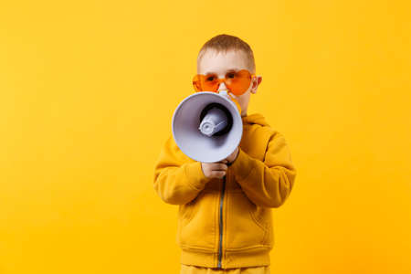 Little fun kid boy 3-4 years old in yellow clothes holding, speaking in electronic megaphone isolated on orange wall background, children studio portrait. People childhood concept. Mock up copy space