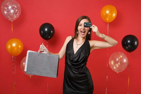 Happy girl in black dress covering eye with credit card holding packages bags with purchases after shopping on bright red background air balloons. Happy New Year birthday mockup holiday party concept