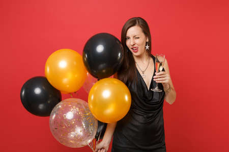 Sexy woman in black dress celebrating blinking licking lips, holding glass of champagne, air balloons isolated on red background. Valentine's Day, Happy New Year birthday mockup holiday party concept
