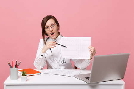 Female doctor sits at desk works on computer with medical document heart ekg in hospital isolated on pastel pink wall background. Woman in medical gown stethoscope. Healthcare medicine concept