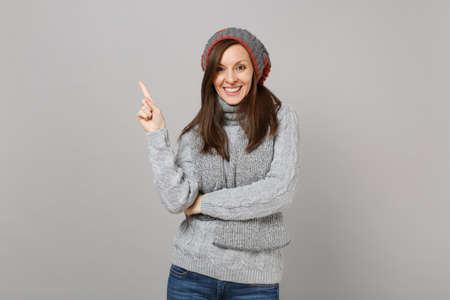 Smiling young woman in gray sweater, hat and scarf pointing index finger up isolated on grey background. Healthy fashion lifestyle, people sincere emotions, cold season concept. Mock up copy space