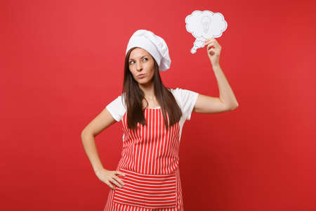 Housewife female chef cook or baker in striped apron white t-shirt toque chefs hat isolated on red wall background. Pensive woman think, hold say cloud with lightbulb idea. Mock up copy space concept Stock fotó